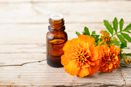 Marigold essential oil and flowers on the wooden board