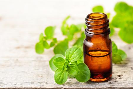 Oregano essential oil and fresh oregano leaves on the wooden board