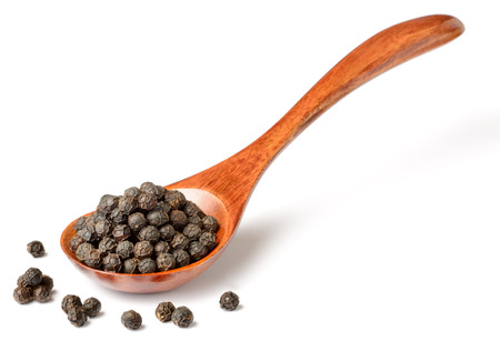 dried black peppercorns in the wooden spoon, isolated on white