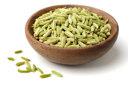 dried herb, fennel seeds in the wooden plate, isolated on white