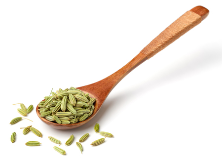 dried fennel seeds in the wooden spoon, isolated on white