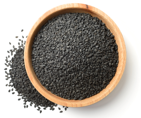 dried black sesame seeds in the wooden plate, isolated on white, top view