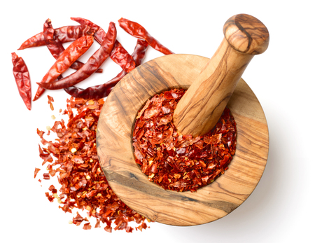 dried red chilli flakes in the wooden mortar, isolated on white, top view