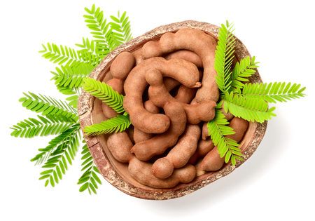 fresh tamarind fruits and leaves in the wooden bowl, isolated on the white background, top view