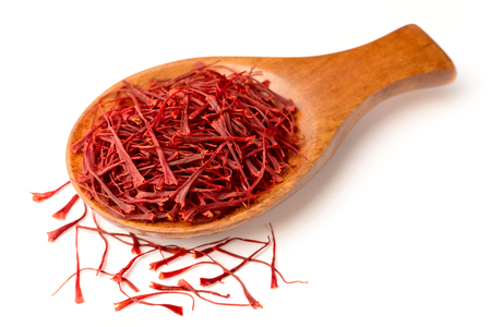 saffron thread in the wooden spoon, isolated on the white background.