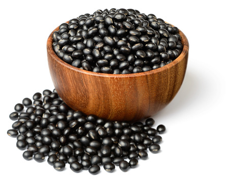 uncooked black beans in the wooden bowl, isolated on white Banque d'images