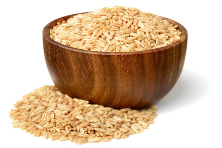 uncooked oats in the wooden bowl, isolated on white
