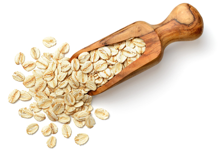 raw oatmeal in the wooden scoop, isolated on white background, top view