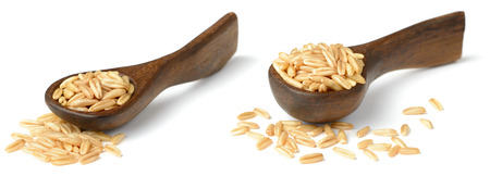 uncooked oats in the wooden spoon, isolated on white background