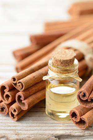 cinnamon oil and cinnamon sticks on the wooden board Standard-Bild