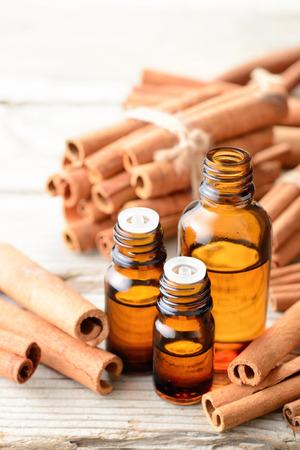 cinnamon oil and cinnamon sticks on the wooden table