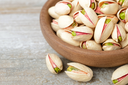 pistachio nuts with shell in the wooden plate, on the wooden board
