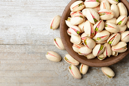 pistachio nuts with shell in the wooden plate