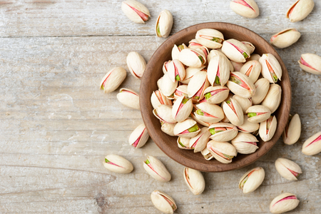pistachio nuts with shell on the wooden board, top view