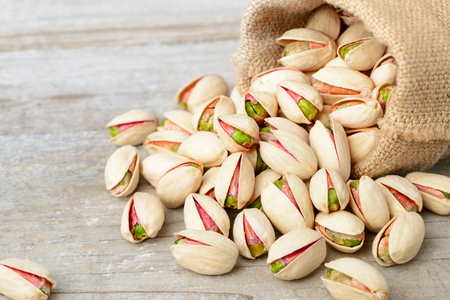 pistachio nuts with shell in the sack, on the wooden board