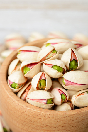 pistachio nuts with shell in the wooden bowl, on the wooden board Standard-Bild