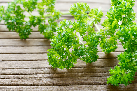 fresh curly parsley leaves on the wooden table Standard-Bild