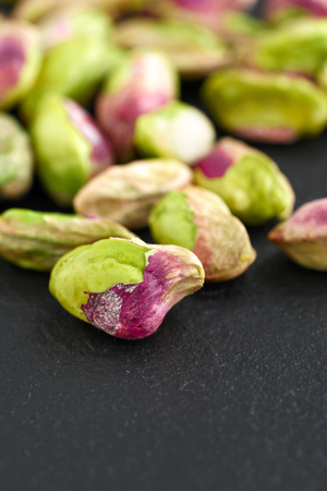 peeled pistachios on the black stone board