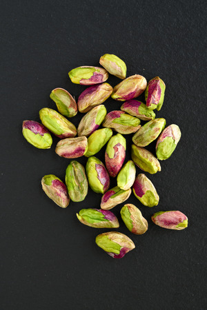 peeled pistachios on the black stone board, top view