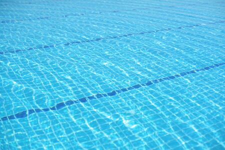 Rippled surface of Swimming pool blue water sun reflecting sleek background Zdjęcie Seryjne - 129807898