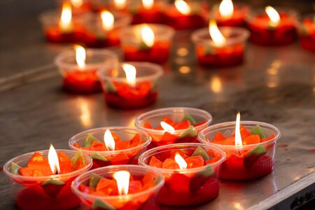 Many burning red flower candles cup at chinese temple Stok Fotoğraf