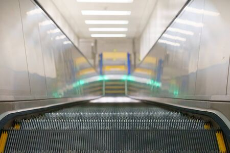 Top view of long empty escalator in a train station