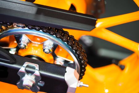 Chain and gear wheel of new yellow motocycle close up Foto de archivo - 129808185