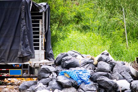 Back of truck with Industrial waste on a landfill Stock Photo