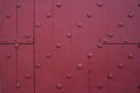 Close up of large old wooden red doors are beautifully decorated