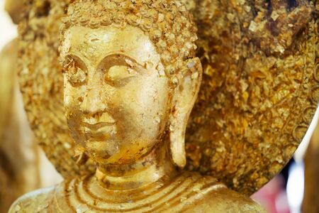 Asian The golden Buddharupa covering with gold leaf background close up