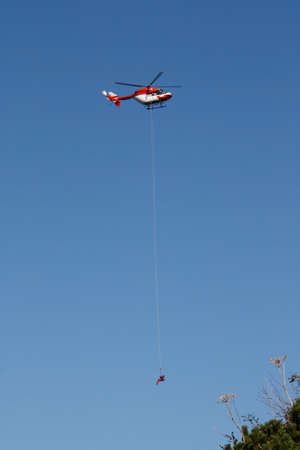 salvaging: Rescue helicopter releasing a man on a rope Stock Photo