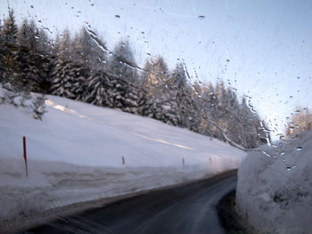 winter road: Wet and slippery winter road as seen through the wind shield Stock Photo