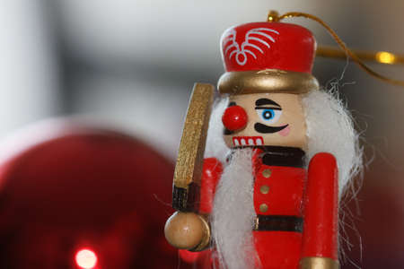 Closeup of a miniature nutcracker in front of a christmas ball photo