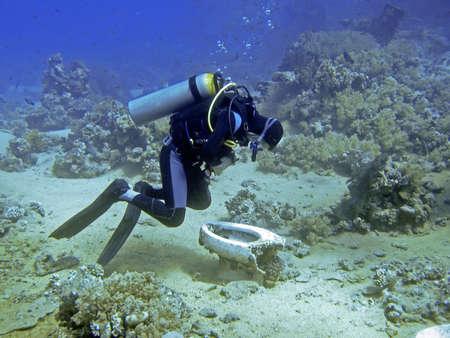 Unidentifiable diver bend over a scrap toilet underwater Standard-Bild