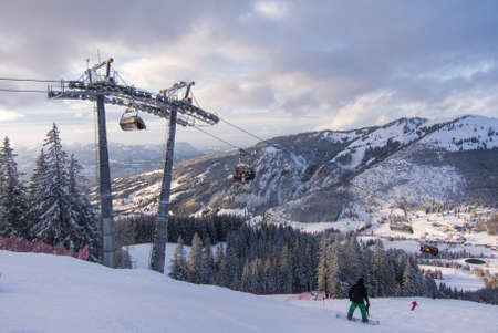 wintersport: Iselerbahn chairlift and some Snowboarders in the German Alps