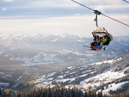 wintersport: Chairlift with un-identifiable skiers hovering over a valley