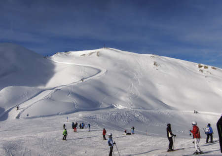 wintersport: Skiers on the slopes of mount  Ifen  in front of a winter hiking path winding up the summit