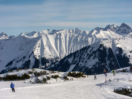 wintersport: Skiers on a slope with the Austrian-German Alps in the background Stock Photo
