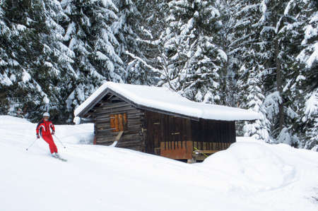 wintersport: Unidentifiable skier in a red skiing suit passing a wooden cabin near a forest slope Stock Photo