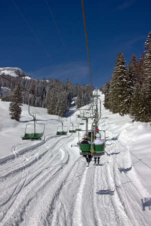 deep powder snow:  Chairlift with unidentifiable skiers up mount Hoher Ifen in the Austrian Alps