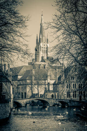 View from the Beguinage bridge to the tower of the Church of our Lady in medieval Bruges, Belgium  photo
