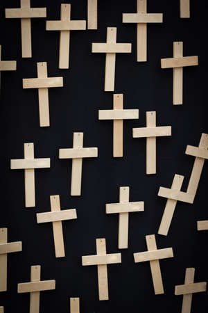 exitus: 25 plain handmade wooden crosses suspended on a black canvas