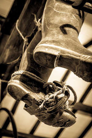 outworn: 19th century rubber boots hanging from a beam in a workshop