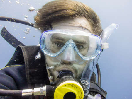 Portrait of a diver under water with mask and regulator photo