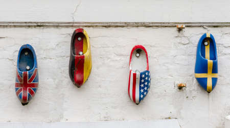 Wood clogs on a wall, painted in the national flag colors of four nations photo