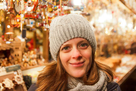 christkindlmarkt: Pretty young girl, wearing a woolen cap, standing in front of an ornament stall at a German Christmas Market Stock Photo