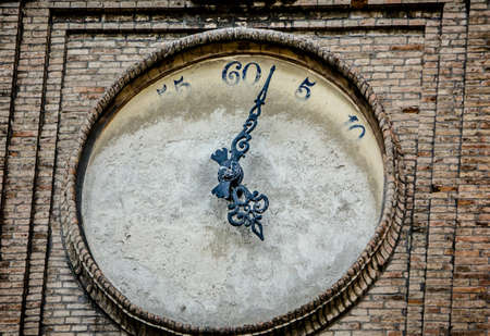 defaced: Close-up of a turret clock with painted-over clock face in Parma, Italy