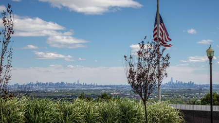View on the Skyline of Manhattan from Eagle Rock Reservation in New Jersey with a US flag in the foreground photo