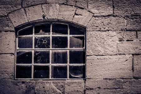 cryptic: Ancient window in a stone cottage with a bullet hole in the glass