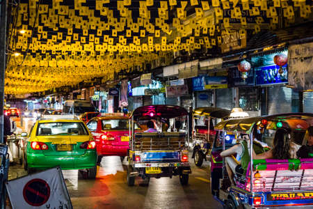 autorick: Bangkok, Thailand - November 1, 2013 - Tourists ride Thai tuk-tuks on a flag-decorated road close by Khaosan Road in Bangkok in November 2013  Editorial